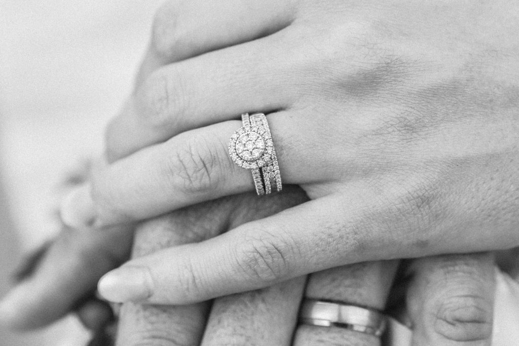 hands with engagement ring and wedding band stack